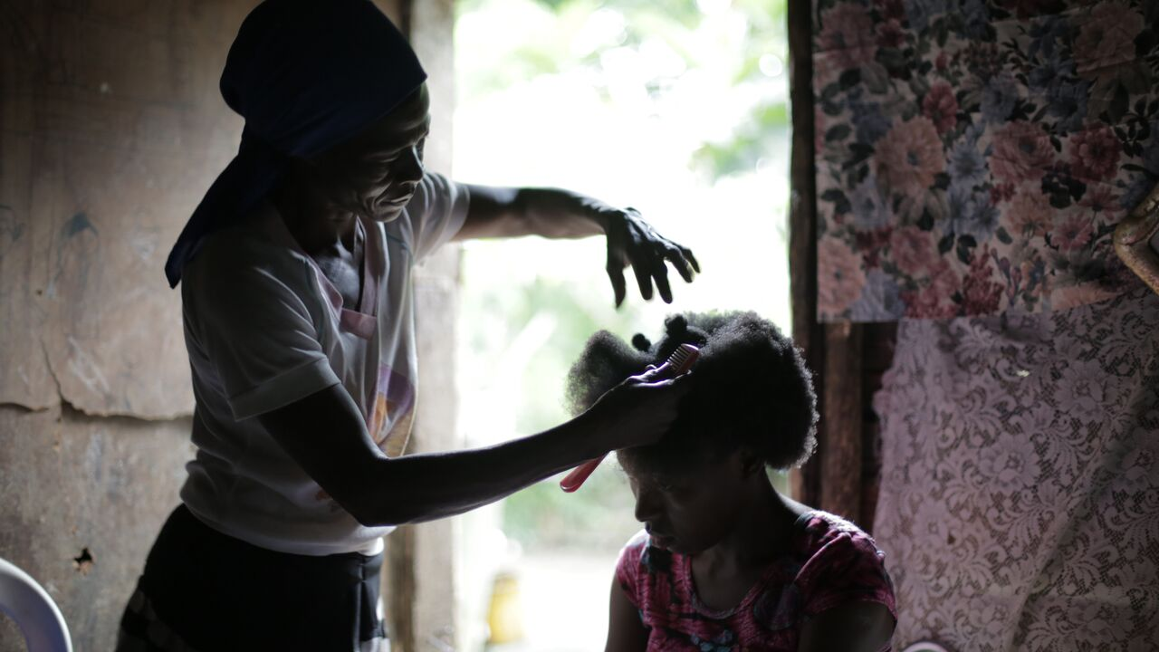 Elena being groomed and her hair brushed by a family member.